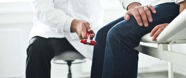 Mediziner untersucht Patienten am Knie